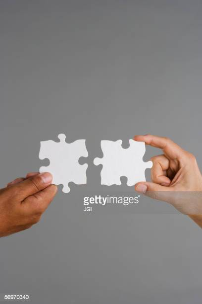 Close up of two hands holding puzzle pieces
