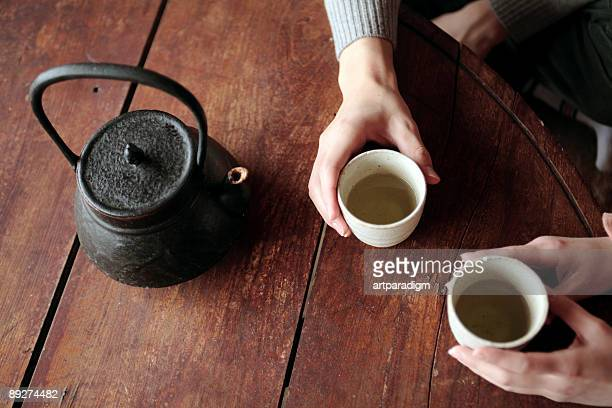Close up of two pairs of hands, holding green tea