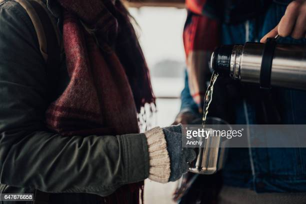 Close up of two passengers who poured hot coffee from a thermos