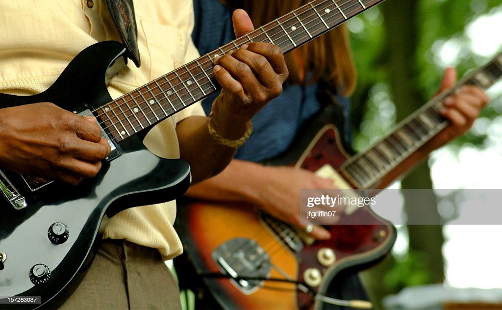 Close up of two people playing guitars