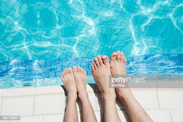 Close up of two people's legs by the pool side