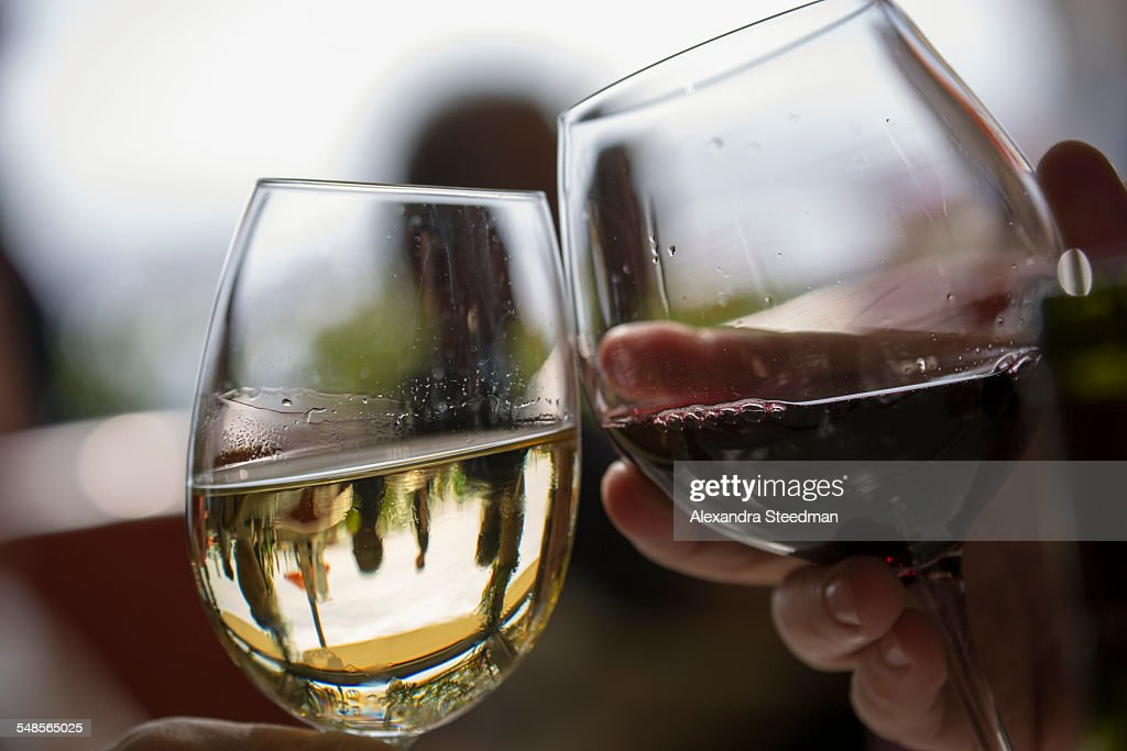 Close up of two wine glasses toasting each other in restaurant