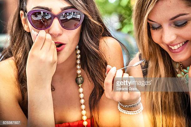 Close up of two young female friends with teaspoons at sidewalk cafe, Cagliari, Sardinia, Italy