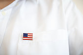 Close up of United State of America pin national flag on white shirt pocket.
