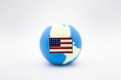 Close up of United State of America pin national flag over mini world ball on white background.