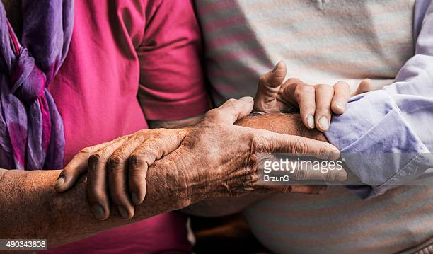 Close up of unrecognizable older couple holding hands.