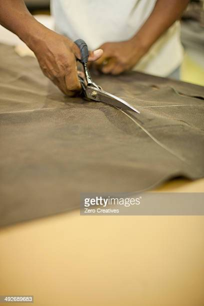 Close up of upholsterer cutting leather with scissors