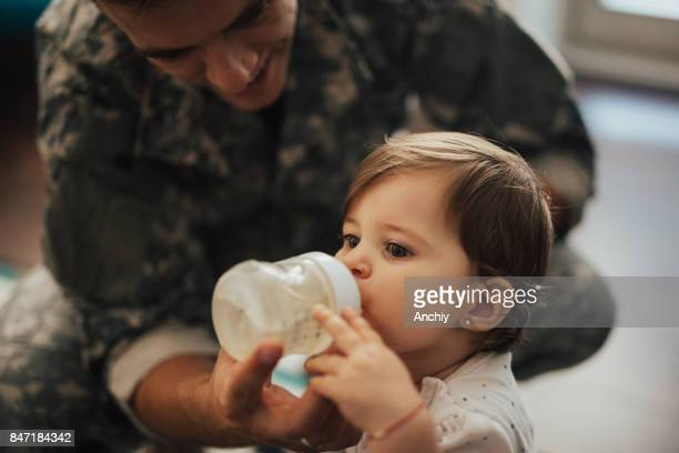 Close up of US soldier father feeding his daughter