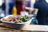Close up color image depicting a white polystyrene container of  freshly prepared vegan and vegetarian take away food for sale at Borough Market in London, UK. The food appears to contain red cabbage,