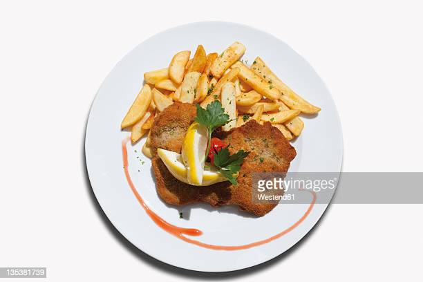 Close up of Viennese Schnitzel with french fried potatoes against white background