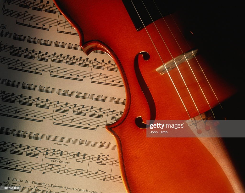 Close up of violin resting on sheet of music : Stock Photo