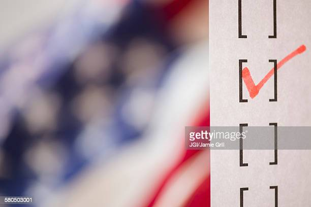 Close up of voting ballot near American flag