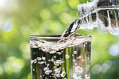 Close up of water flowing from drinking water bottle into glass on blurred green nature bokeh background, healthy drinking clean water concept