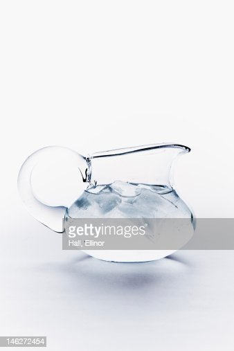 Close up of water with ice cubes in jug on white background