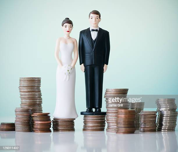 Close up of wedding cake figurines on stacks of coins