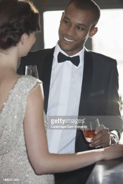 Gros plan de bien habillé couple boire des cocktails au bar