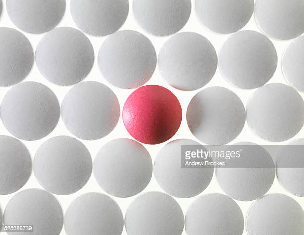 Close up of white pills and one red pill