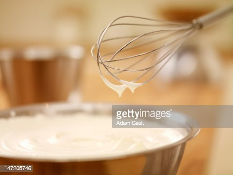 Close up of wire whisk over bowl of cream : Stock Photo