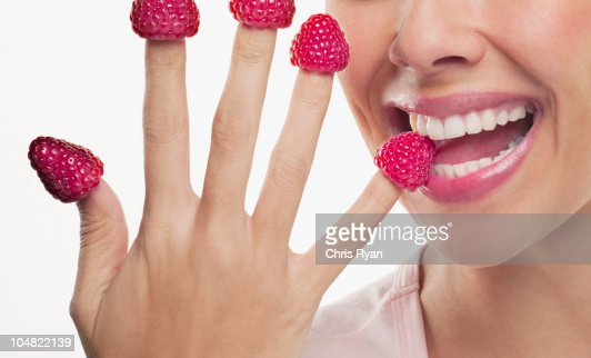 Close up of woman biting raspberries on fingertips : Stock Photo