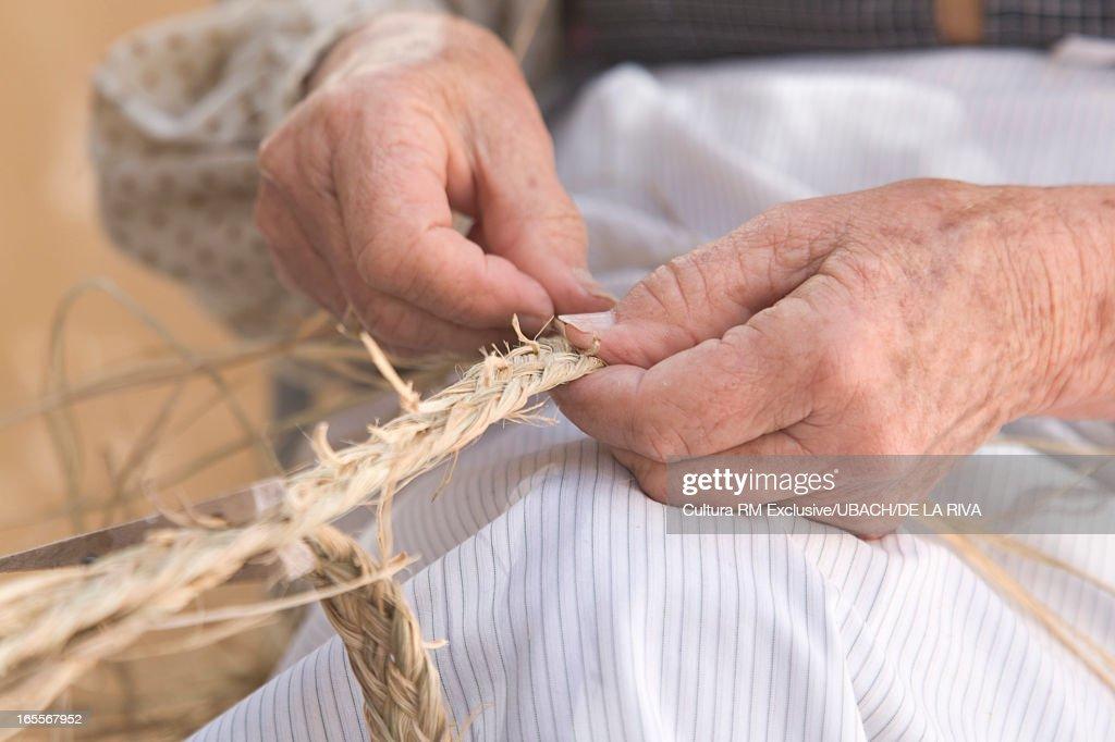 Close up of woman braiding straw