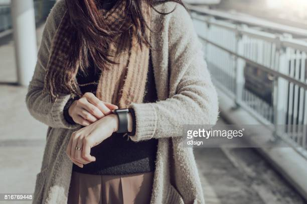 Close up of woman checking her smart watch in city