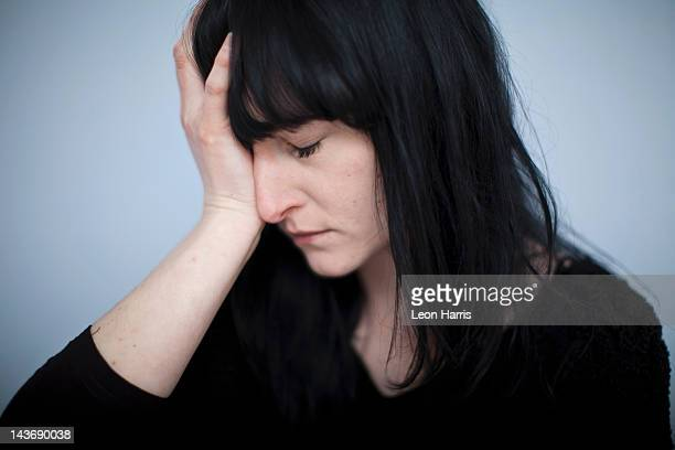 Close up of woman clutching her head