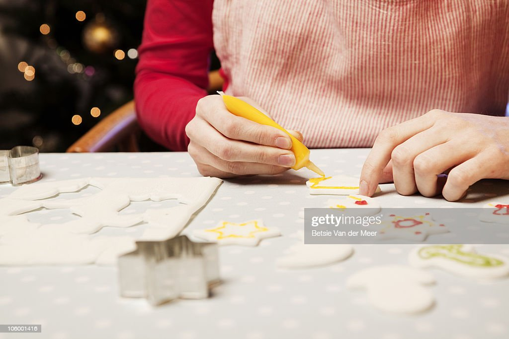 Close up of woman decorating cake decorations.