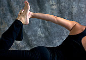 Close up of fit athletic woman doing half bow yoga pose showing arm and leg with hand holding foot in studio against a mottled background.
