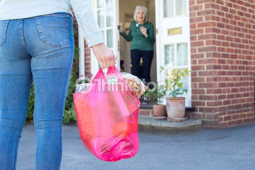 Close Up Of Woman Doing Shopping For Senior Neighbor : Stock Photo