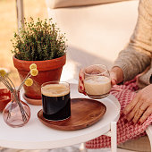 Close up of woman drinking irish coffee liqueur Woman sitting in greenhouse conservatory in sunlight drinking drink and cofee close up of glass.