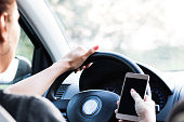 Close up of woman using cell phone and text messaging while driving a car.