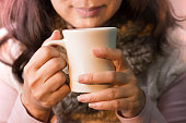 Close up of woman hands holding a cup of coffee.  Female in winter fashion clothes enjoying hot drink with smiling face,selective focused.