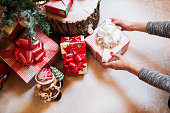 Close up of woman hands putting down a gift box under a Christmas tree.