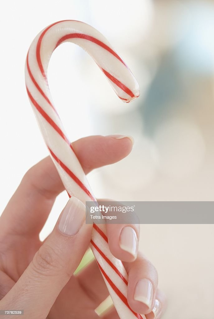 Close up of woman holding candy cane