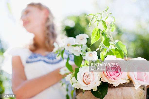 Close up of woman holding flowerpot with roses