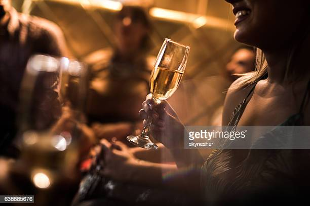 Close up of woman holding glass of Champagne in nightclub.