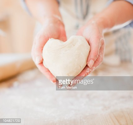 Close up of woman holding heart-shape dough : Stock Photo