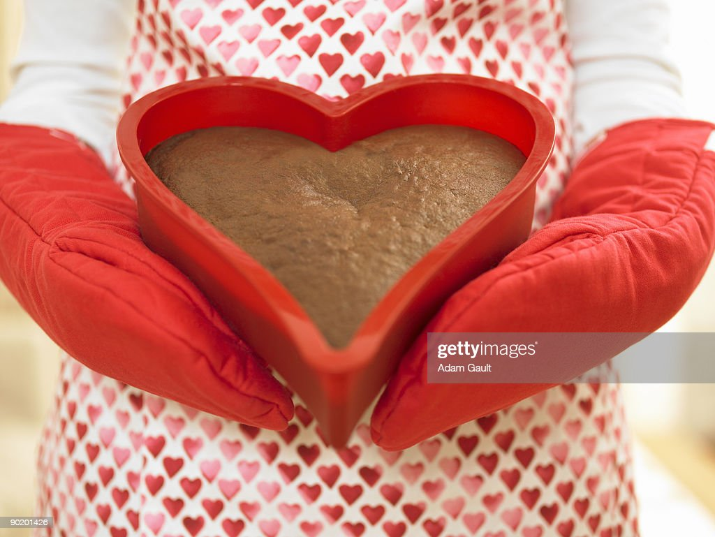 Close up of woman holding heart-shaped cake : Stock Photo