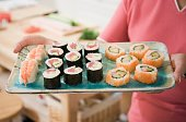 Close up of woman holding tray of sushi