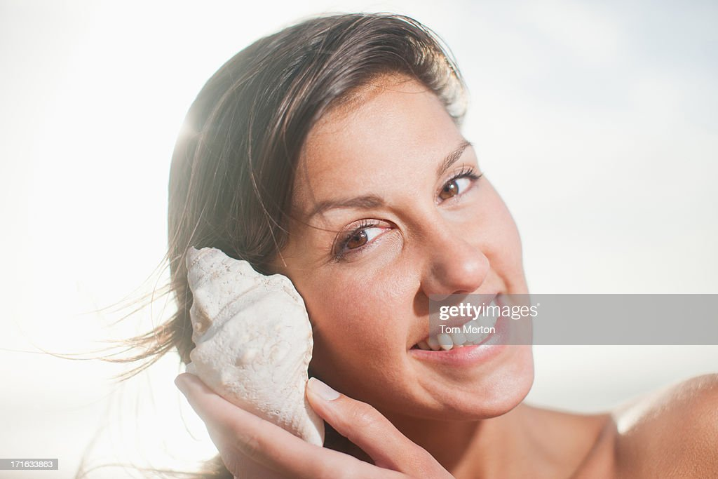 Close up of woman listening to seashell : Stock Photo