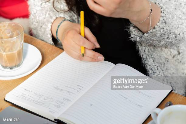 Close up of woman making notes, sitting in cafe, drinking coffee.