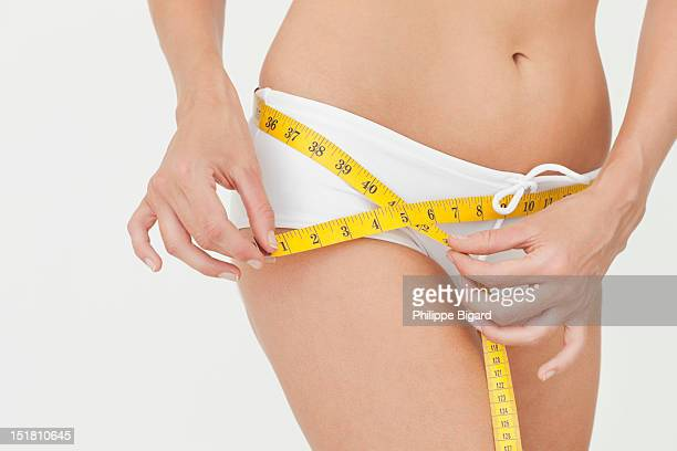Close up of woman measuring hips with tape measure