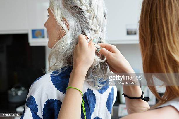 Close up of woman plaiting senior woman's hair