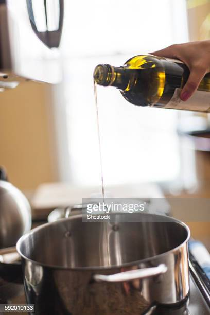Close up of woman pouring olive oil into pot