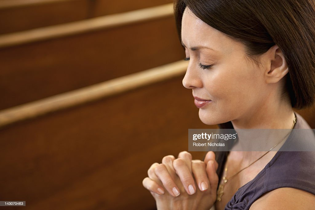 Close up of woman praying in church : Stock Photo