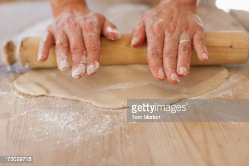 Kitchen Counter Close Up close up of woman rolling dough with rolling pin on kitchen