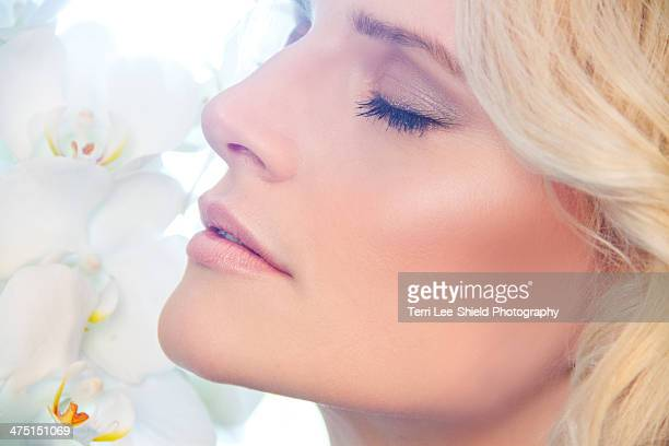 Close up of woman smelling orchids