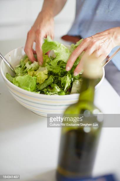 Close up of woman tossing salad