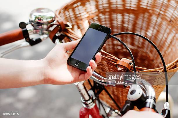Close up of woman using smart phone on bike