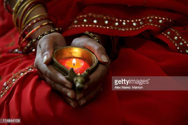 Close up of woman wearing red sari and holding lit candle